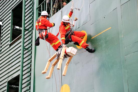 图为现役代表队正在参加山岳下降救援操竞赛。
