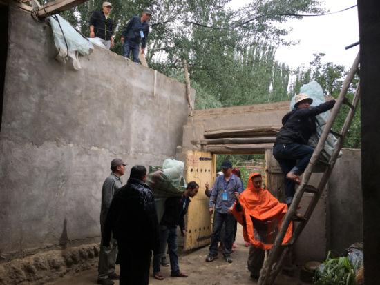 工作队冒雨帮村民盖篷布,防止房屋漏水。塔夏洪・艾散正在上房屋。